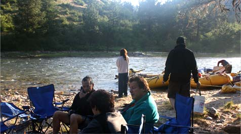 group of people relaxing next to river